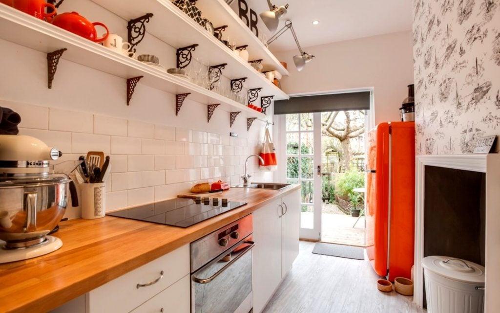 Увеличить визуально пространство в вытянутой кухне можно, заменив навесные шкафы полками