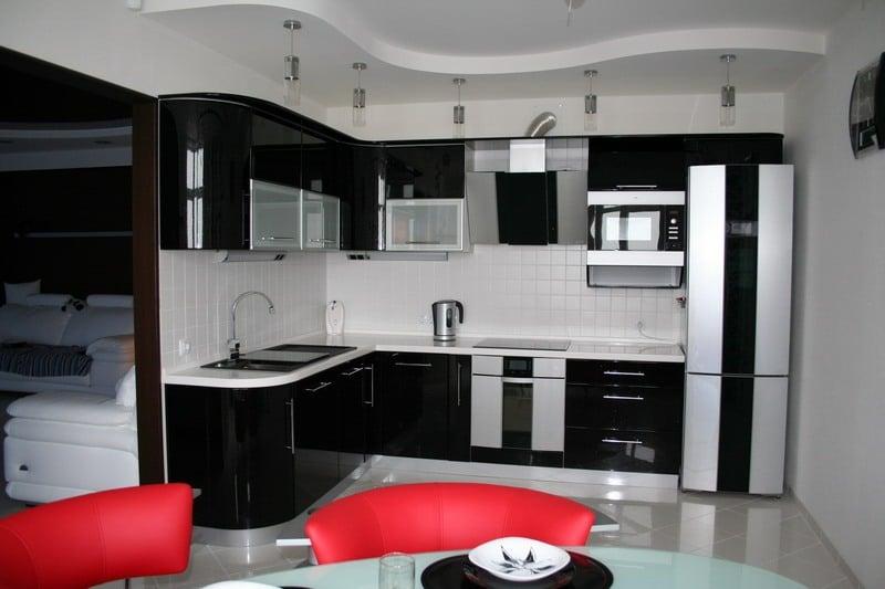 Одноуровневый потолок позволит визуально разделить кухню с помощью осветительных приборов на 2 зоны