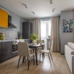 Кухня-студия с бежевыми шторами. Акцент сделан на картину