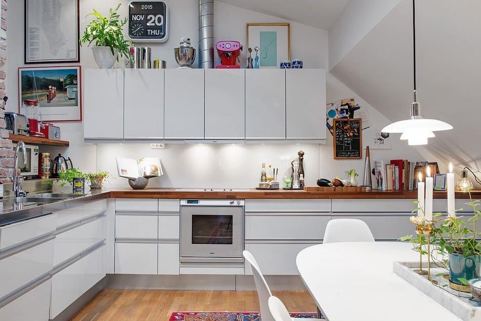 Белая кухонная зона с дополнительными аксессуарами в виде картин и комнатных цветов.