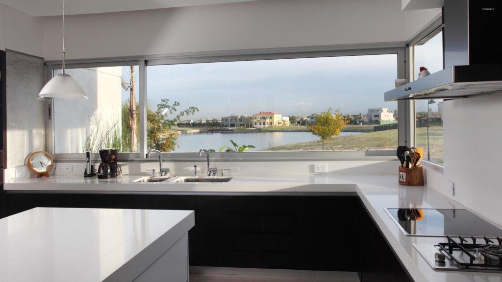 Кухня в светлых тонах проектируется с широкими панорамными окнами и украшается длинными портьерами