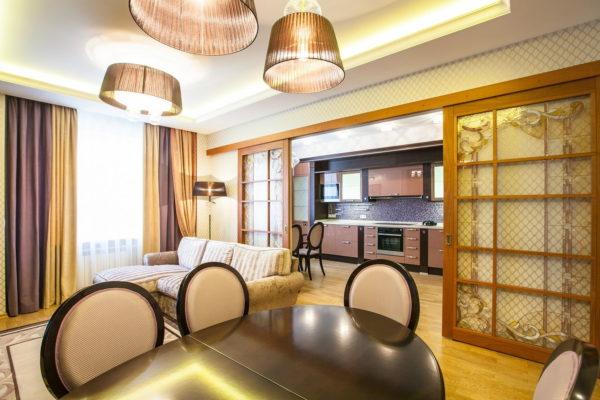 Пример раздвижной конструкции в интерьере гостиной и кухни