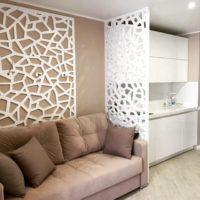 Резная перегородка сочетается с оформлением стены в гостиной