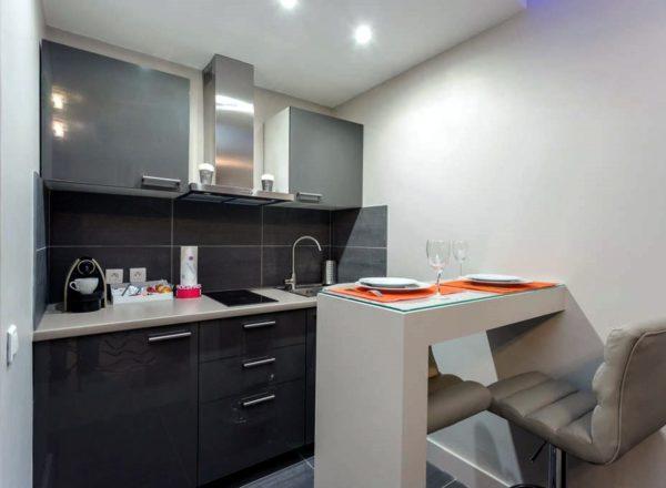 Маленькая кухня-студия с прямым кухонным гарнитуром